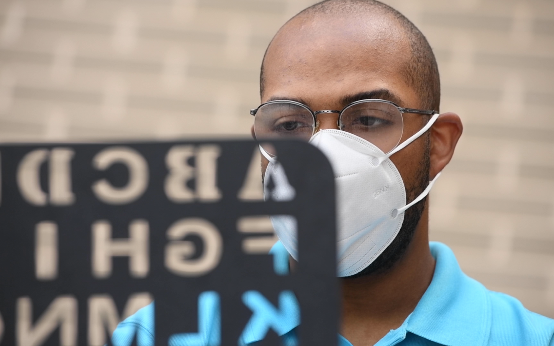 A man wearing a mask looks at a board containing the letters of the alphabet.