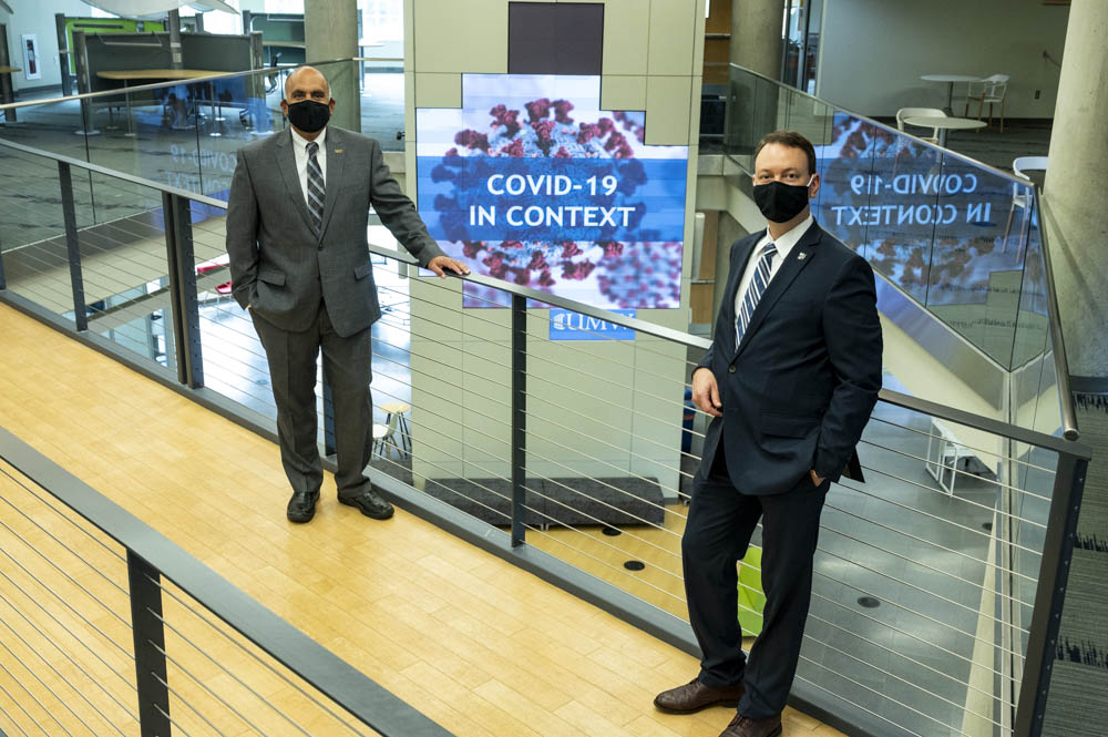 Two men in suits and cloth masks lean against a rail , and a screen behind them shows COVID-19 In Context