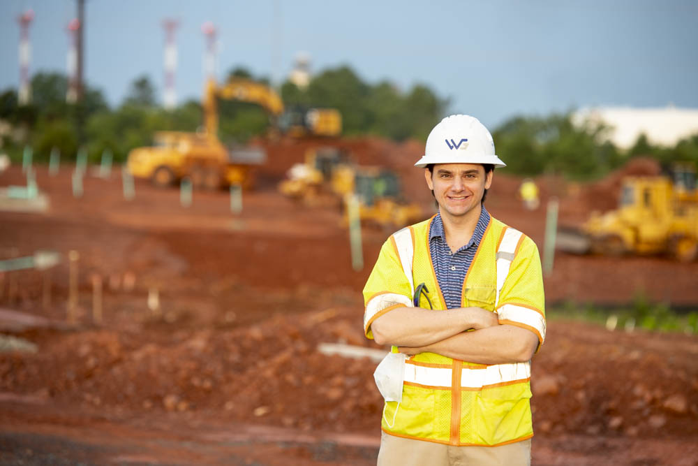 A man wearing a yellow vest and hardhat stands in front of earthmoving equipment