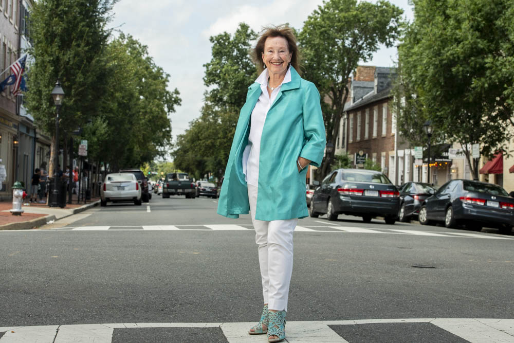 A woman with a blue jacket stands on a city street with a shops lining the street.